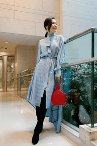 A woman in blue dress carrying ATENA RED PURSE-SLING BAG, a red bag, red handbag, with minimalist look from MDLR