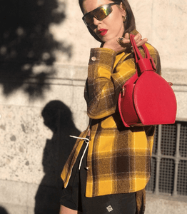 A woman carrying in her shoulder ATENA RED PURSE-SLING BAG, a red bag, red handbag, with minimalist look from MDLR