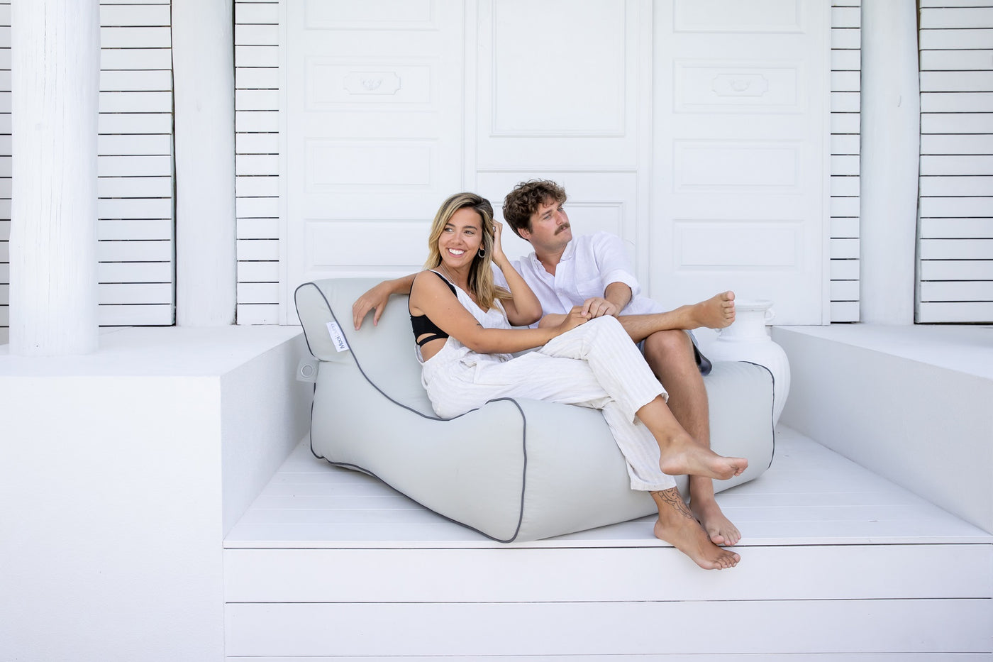 Man and Woman relaxing on a Mooi Living Outdoor Lounger Bean Bag. Shop Laguna Lifestyle for all your pool and outdoor lifestyle accessories.