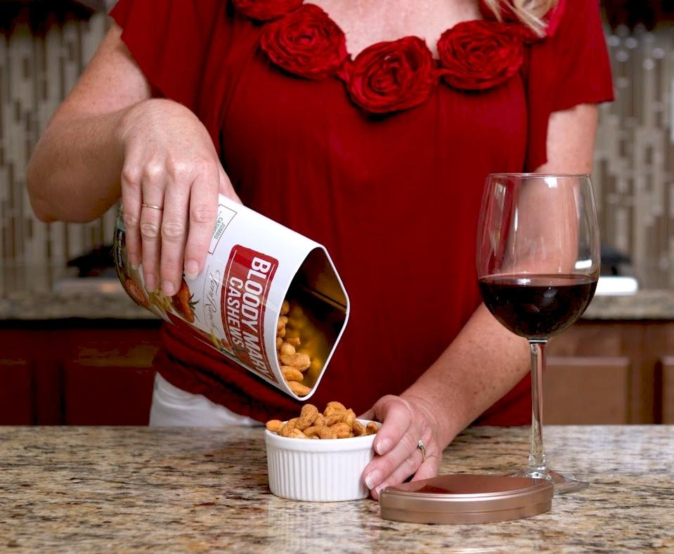 Copper Cocktail Nut Tin Collection Gourmet Nuts - woman pouring out Bloody Mary cashews into ramekin