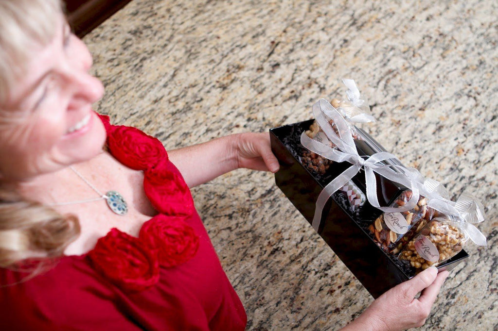 Metropolitan in Unique Gifts & Gift Baskets - Woman presenting basket wrapped in bow