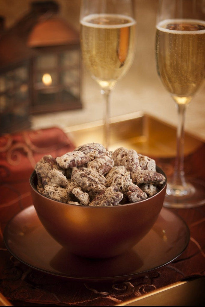 Cinnamon Spice Pecans in decorative bowl next to champagne glasses