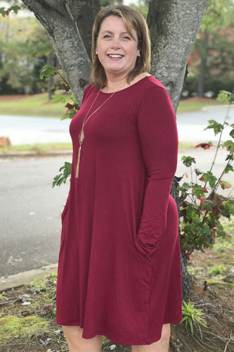 Our I've Got Plans Dress is a staple Fall closet item. She is a classic long sleeve t-shirt dress. She is super soft and features two side pockets. She has a little bit of a flare shape that gives her a relaxed fit. She is a beautiful Cabernet color and is a part of our Curvy Collection. Dress her up with a statement necklace or a cozy blanket scarf and booties for the perfect Fall date night look.