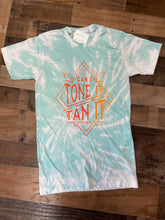 "Load image into Gallery viewer, Our Tan it Tone it Tee is a soft to the touch aqua bleach dyed tee. She features a printed design that reads, ""If you Can't Tone it Tan it.""   These shirts are hand dyed. Color, bleach, and dye pattern will vary on each shirt."