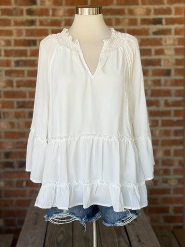 Our Cute as a Button Top was exactly what your Closet is Missing! She is a solid, V-neck,  tiered top featuring smocking detail at neckline. She is perfect to match with any color bottoms you ight have! She would be adorable paired with a distressed jean and flats