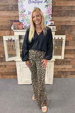 Load image into Gallery viewer, Stay wild in our Born to be Wild Pants. She is a leopard print flare style pant complete with a zipper closure and functional back pockets. With a live edge hem, she is the perfect statement piece to have in your closet. Pair her with your favorite graphic tee for a casual look or with a trendy crop top for a night out.