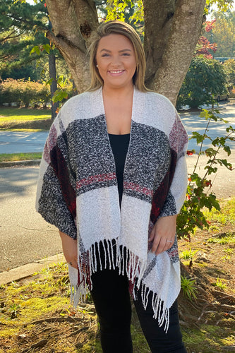 Our Plaid You Came Poncho is a Burgundy, Black, and White plaid print drape style poncho. She is a soft sweater knit material that makes her the perfect Fall accessory. She features a frayed hemline and is an open front style. She has a relaxed fit that makes her both comfy and cozy. This poncho cardigan is one size, but is very Curvy friendly. We see her being used for Fall and Winter family pictures!