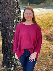 Our Heart Stopping Sweater is a perfect knit basic for this season! She has a slight V-neckline, long rolled up sleeves, and a vented hemline which adds flare to this top. She is a vibrant burgundy color which pairs best with Dark Denim!