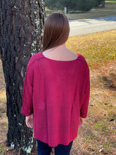 Load image into Gallery viewer, Our Heart Stopping Sweater is a perfect knit basic for this season! She has a slight V-neckline, long rolled up sleeves, and a vented hemline which adds flare to this top. She is a vibrant burgundy color which pairs best with Dark Denim!