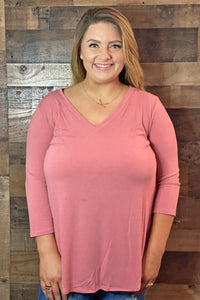 Our Basic Principles Top is the ideal layering top for Fall. She is a soft dusty rose 3/4 sleeve top with a v-neckline. She has a round hem with plenty of length to pair with leggings. She is going to be so cute paired with a vest and blanket scarf! She is also available in Black and Charcoal. She is a part of our Missy and Curvy Collections.  Model is wearing a size 2X.   Material Content: 57% Polyester/38% Rayon/5% Spandex