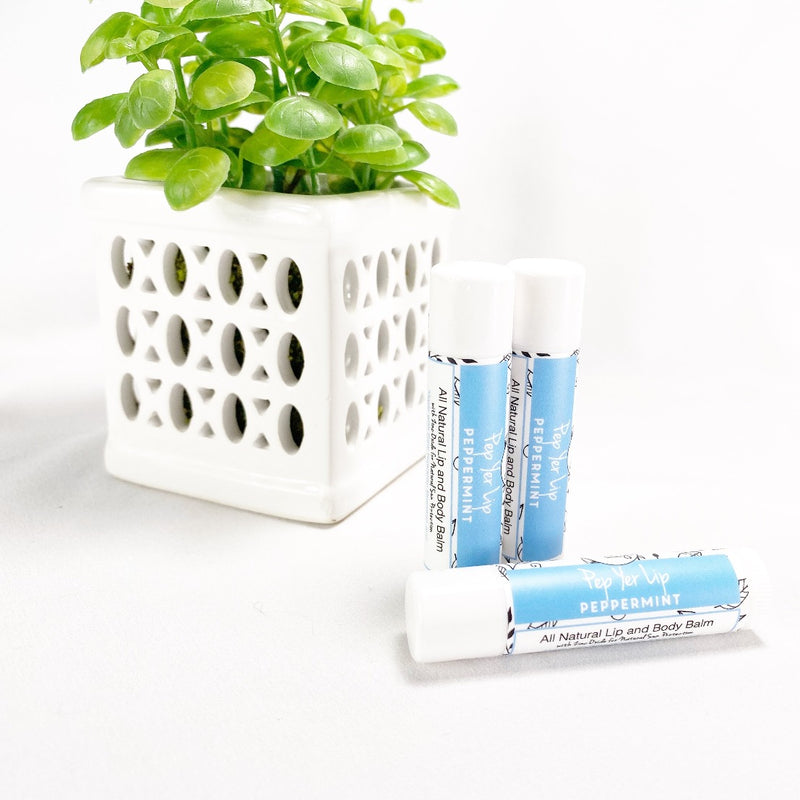 Per Yer Lip - Peppermint Lip Balm. Image shows three lip balms with green plant in background.