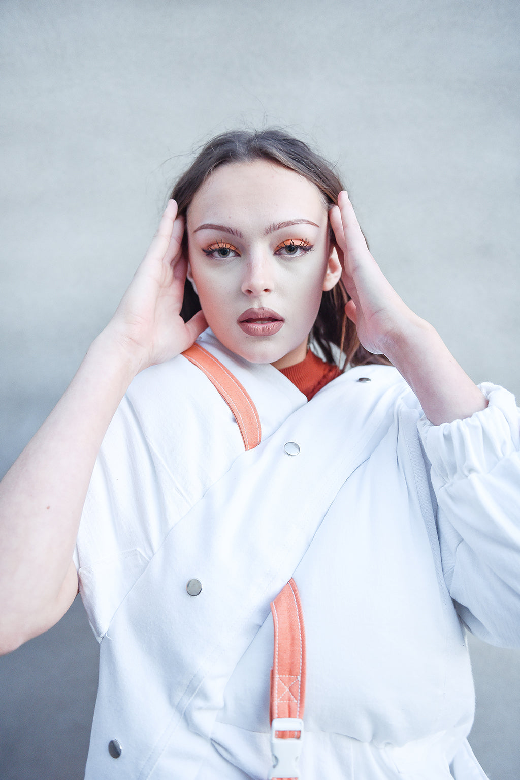 Beautiful portrait of brunette girl with orange makeup looks at the camera wearing a recycled white denim puffer coat with orange straps