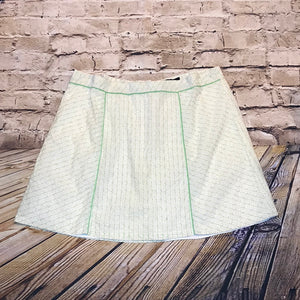 Torrid white mini tennis skirt with green and yellow polka dots and lime green piping.
