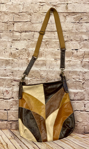 Brown leather purse in geometric altering pattern with dark brown, cream, and tan.  Canvas strap with inside pockets and zip closure.