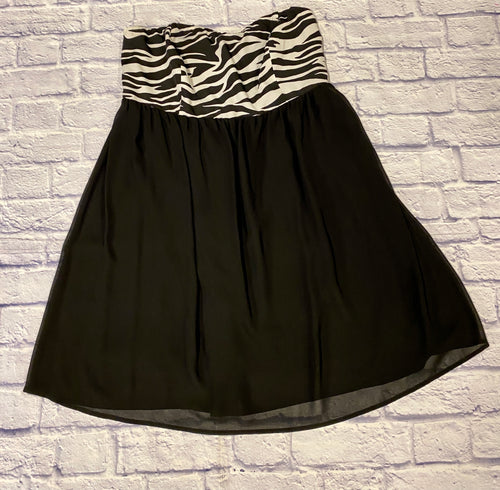 Sleeveless mini cocktail dress in black and white zebra print.  A-line hem with gathered top material in zebra and flowy chiffon skirt bottom in solid black.