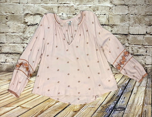 Light pink blouse with embroidered floral sleeve pattern and embroidered cuffs, v neck collar.