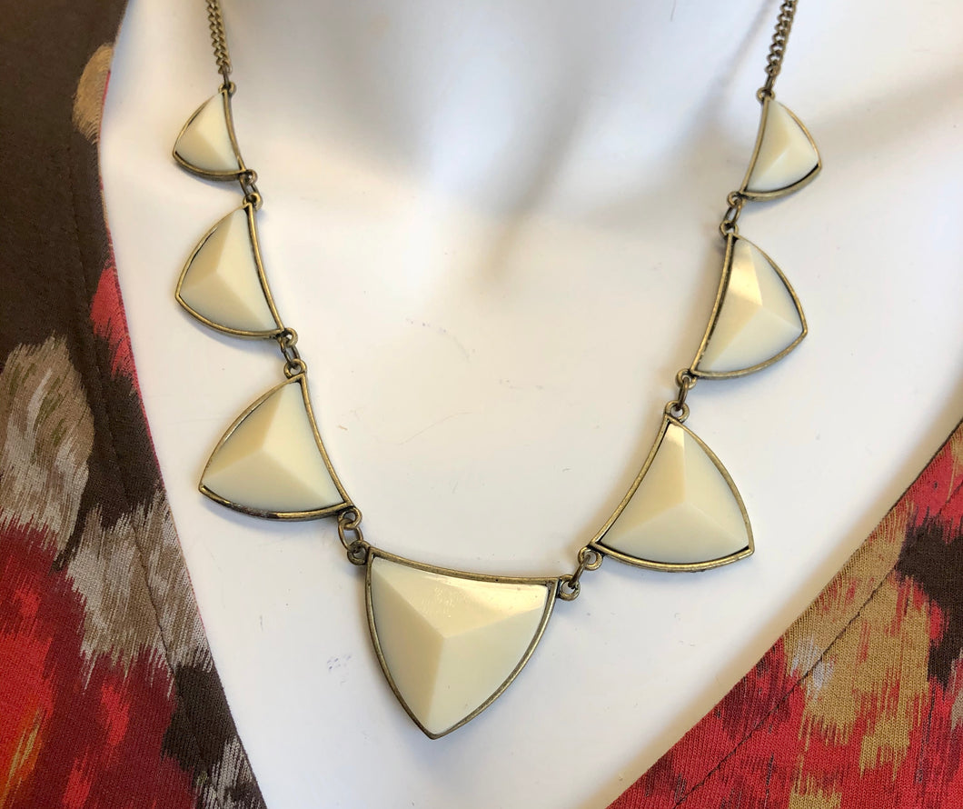 Ceramic ivory style necklace with 7 teeth in gold plate.