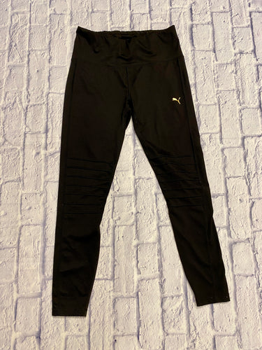 Puma active leggings in black with front thigh pattern and calf contrasting material.  Gold Puma logo on left hip.