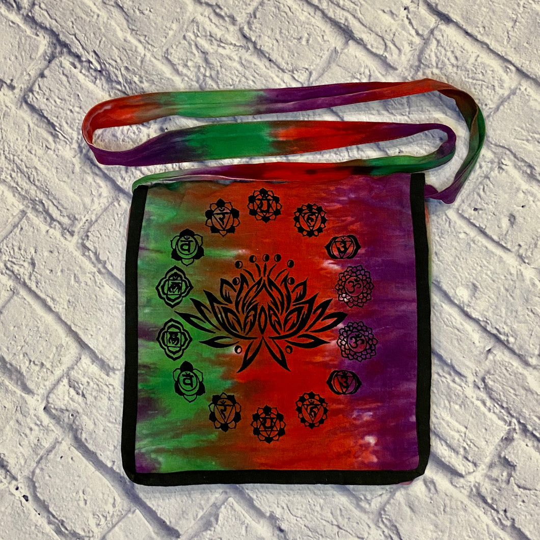 Gypsy Rose tie dye fabric crossbody purse in green, red, and purple with lotus flower on front.  Flap closure with smaller pocket in front and main zipper closure.