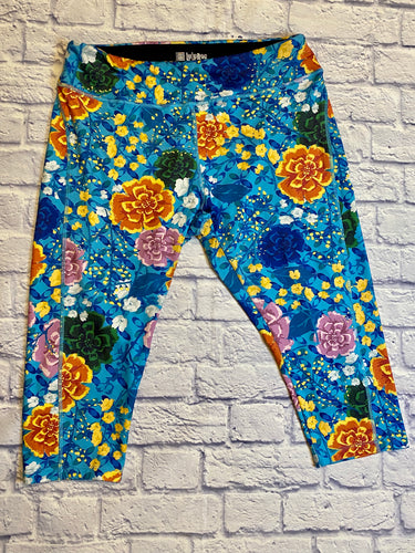 Lularoe turquoise active cropped pants with orange, purple, and yellow floral pattern.  Elastic waistband.