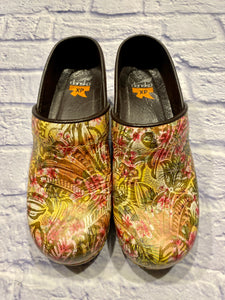 Brand new Dansko clogs with yellow, pink, green, and orange floral pattern.  Brown leather piping around opening.