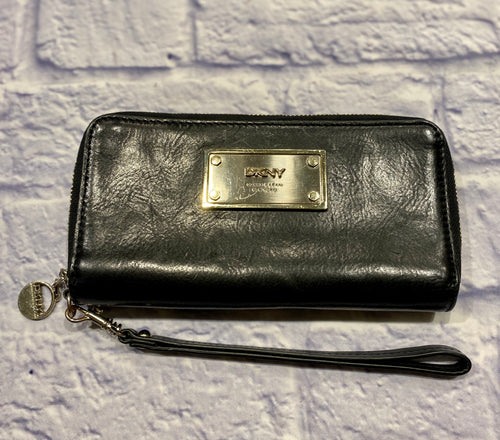 DKNY black leather wristley with silver nameplate on front.  Black leather detachable strap.  Two separate zip pockets, one has credit card slits and the other holds cash/coins.  Second pocket's zipper is broken, easy to replace.  Silver hardware.