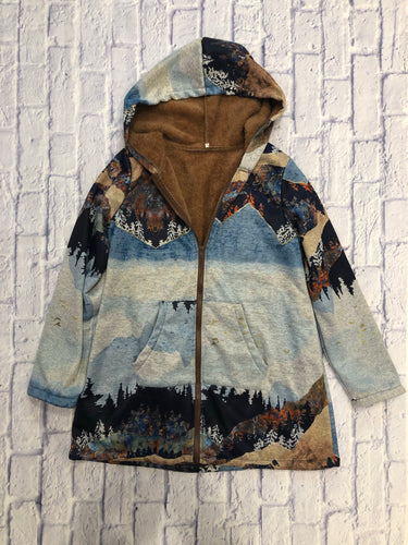 Mountain, forest, and skyline patterned jacket in blues and browns.  Lined with brown sherpa, zip front, with hood.