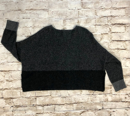 Cropped Eileen Fisher cashmere sweater in block black and grey with light grey cuffs.