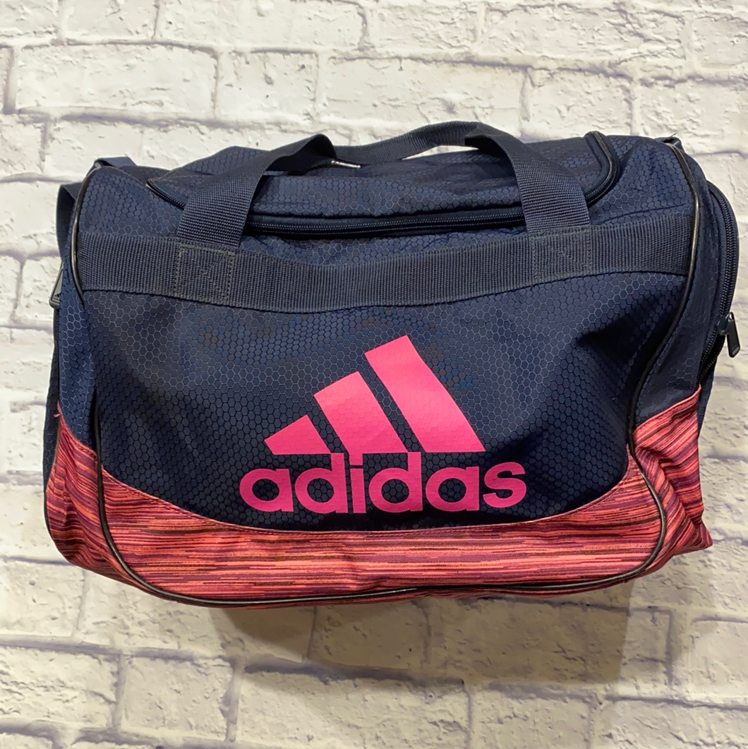 Adidas navy blue M/L duffel bag with pink logo and bottom with grey interior lining.