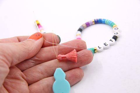How to attach a tassel to a beaded bracelet, by WomanShopsWorld