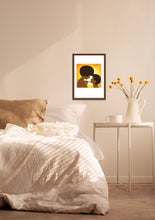 Load image into Gallery viewer, Framed art print of a black mom and daughter with afros, hanging on a bedroom wall near a bed, bedside table and a yellow houseplant