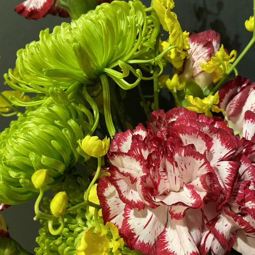 Green spider chrysanthemums and colourful carnations interwoven with bright yellow orchids.