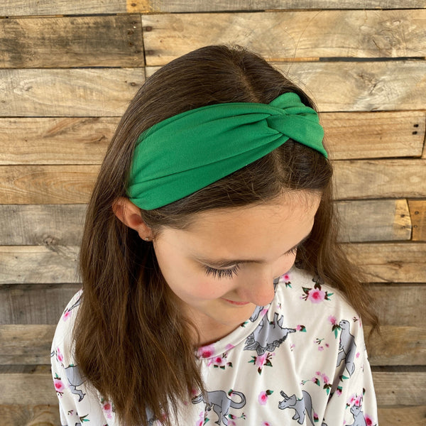 solid kelly green faux knot twist headband on head top view