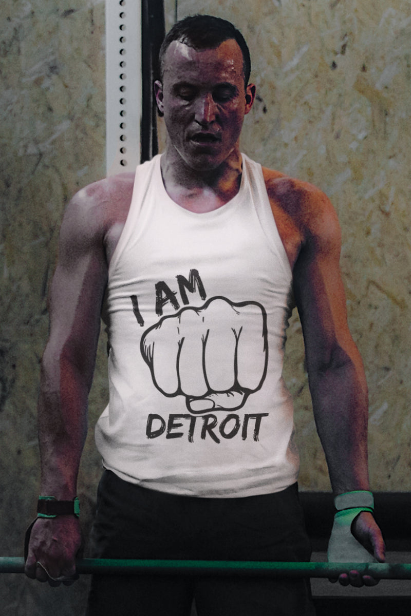 Weightlifter holding barbell wearing a white tank top with black I Am Detroit Fist logo printed across the front