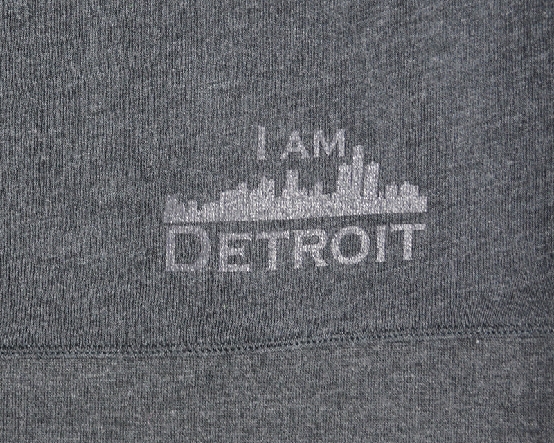 Close up of I Am Detroit logo near hem at bottom on the back of a gray hooded sweatshirt