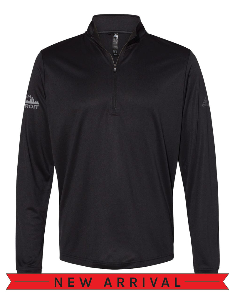 Front view of a Black Cool Down Quarter-Zip Adidas long-sleeve pull over featuring a dark grey Adidas logo on the left arm and a grey I Am Detroit logo on the right arm