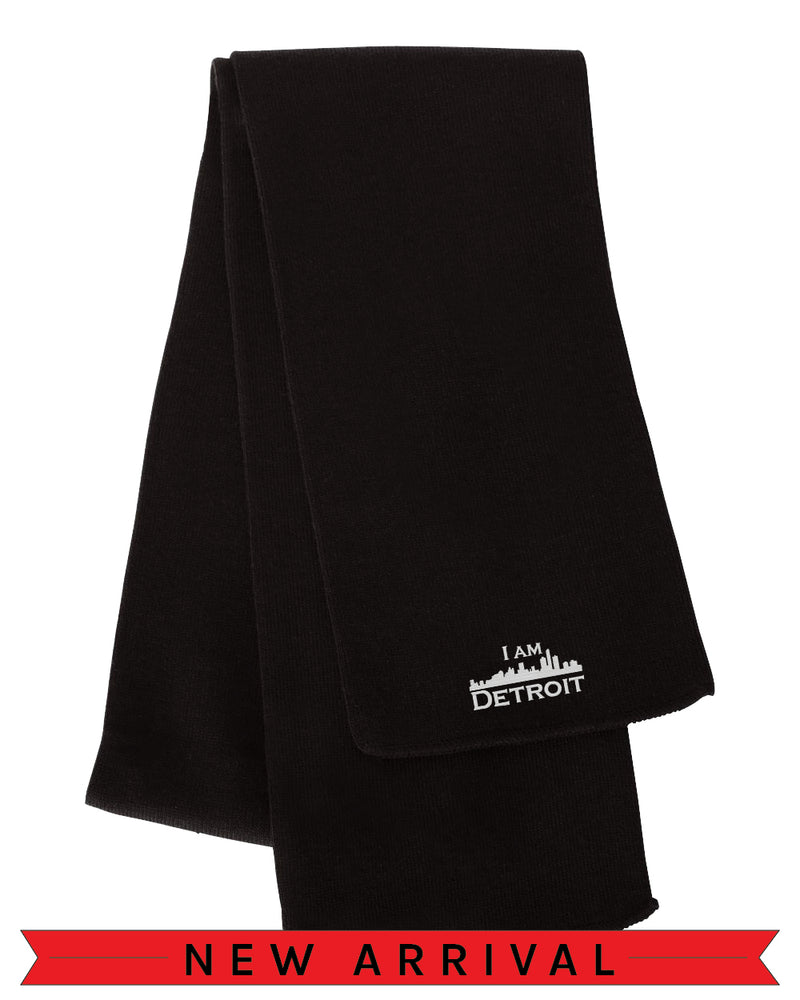 Long Black acrylic scarf with embroidered white I Am Detroit logo near the edge.