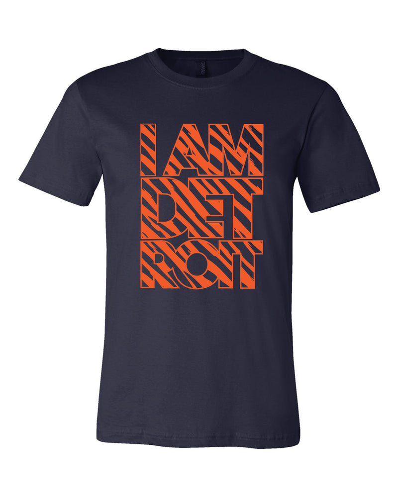 Orange tiger stripes fill large block lettering that reads I Am Detroit on the front of a navy blue T-shirt