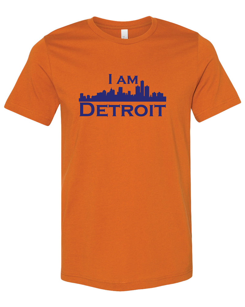 Orange colored short sleeve t-shirt with large dark blue I Am Detroit logo printed across the chest