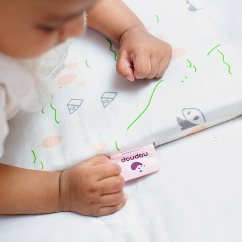 Baby doing tummy time on a NapNap mat