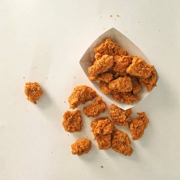 Photograph: Bartleby's Seitan Nuggets. Some of the nuggets are nestled into a white fry boat, and just as many are spilled out over the side, with some delicious crumbs of the southern-friend hand-battered crust scattered about. Nuggets are view from above over a plain white background.