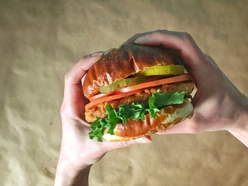 Photograph: A Bartleby's Deluxe sandwich held between two hands over a brown paper background. Sandwich contains a Bartleby's southern-fried Crispy Cutlet, lettuce, tomato slices, pickle slices, all stacked between a pretzel bun.