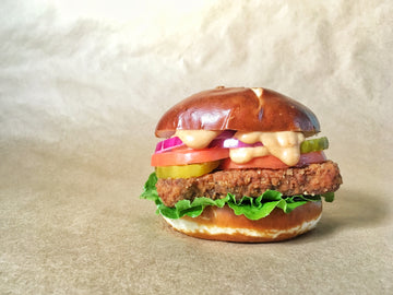 Photograph: A Bartleby's Deluxe sandwich sits directly upon a brown paper backdrop. Sandwich contains a Bartleby's southern-fried Crispy Cutlet, lettuce, tomato slices, pickle slices, red onion slices, a dripping generous drizzle of Bartleby's Original Special Sauce, all stacked between halves of a pretzel bun.