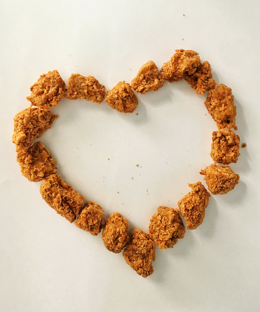 Photograph: Bartleby's Seitan Nuggets, arranged in a heart shape. Some delicious crumbs of the southern-friend hand-battered crust are scattered about. Nuggets are viewed from above over a plain white background.