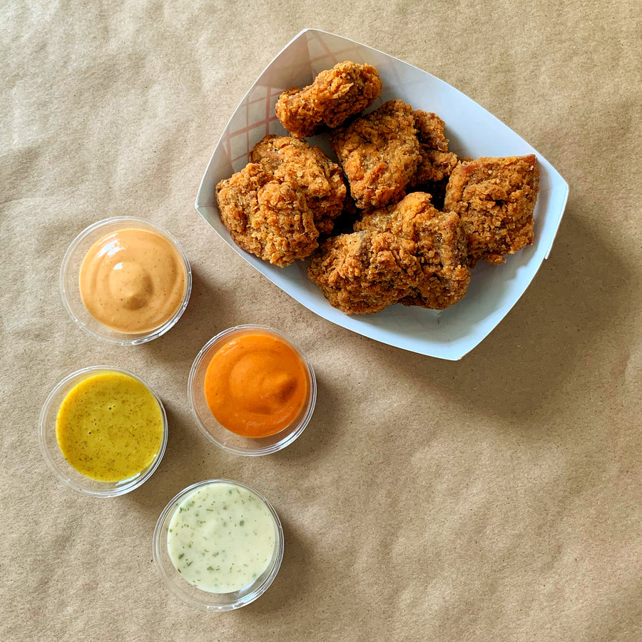 Photograph: Bartleby's Seitan Nuggets, nestled into a white and red-striped fry boat. Four small service tubs of Bartleby's Signature Sauces are arranged nearby. Items are viewed from above over a brown paper backdrop.