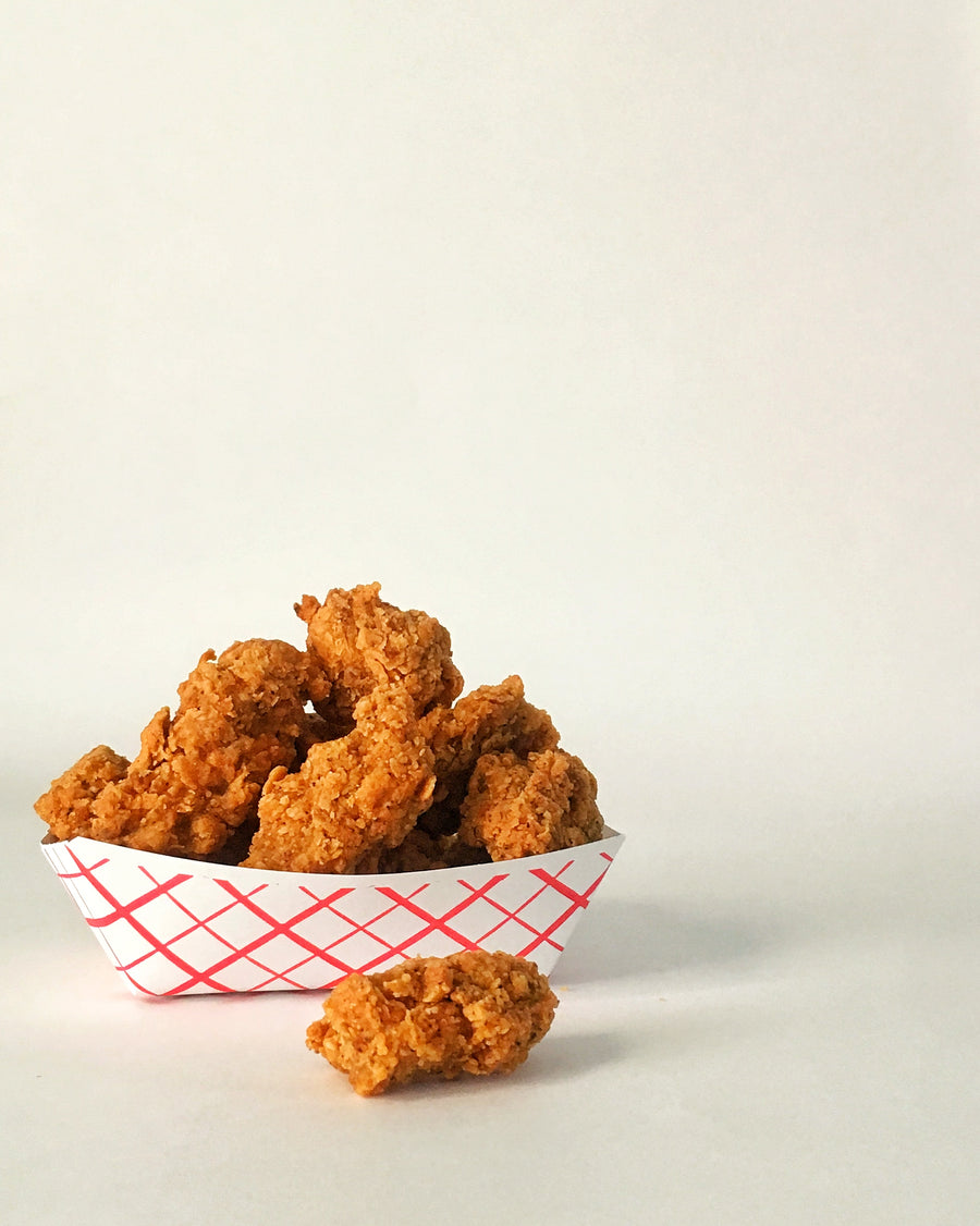 Photograph: Bartleby's Seitan Nuggets. Most of the nuggets are nestled into a white and red-striped fry boat, but one rascally nugget has escaped and is sitting outside the boat. Nuggets are viewed in profile against a plain white background.