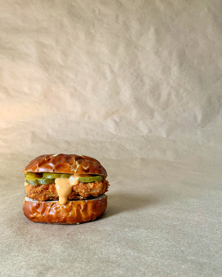 Photograph: Bartleby's Original Sandwich sits directly on a brown paper backdrop and is viewed in profile. The sandwich contains a Bartleby's southern-fried Crispy Seitan Cutlet, slices of dill pickle, and a drippy drizzle of Bartleby's Original Special Sauce, all stacked between halves of a pretzel bun.