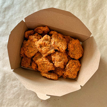 Photograph: Bartleby's Seitan Nuggets, lots of them, piled into a brown paper serving box. Nuggets are viewed from above over a brown paper backdrop.