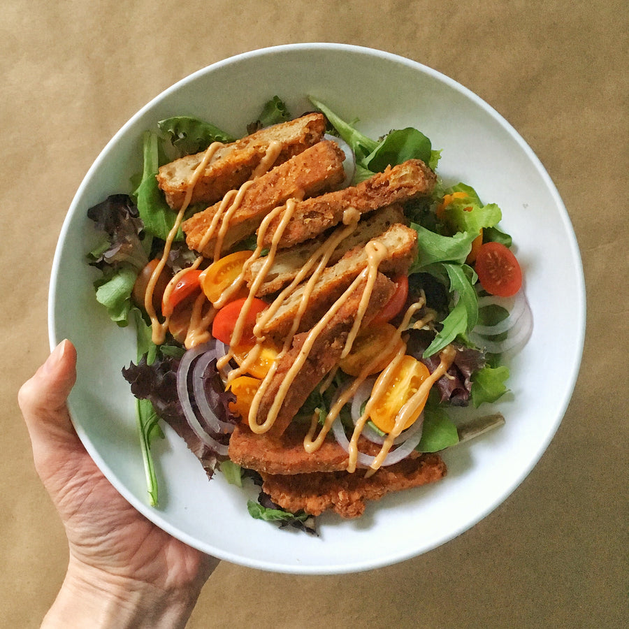 Photograph: One hand holding a white bowl containing a salad over a brown paper background. The salad consists of a Bartleby's southern-fried Crispy Seitan Cutlet, sliced into strips, mixed lettuce greens, halves of grape tomatoes, rings of sliced red onion, and a zig-zag drizzle of dressing.