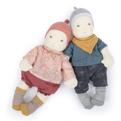 Moulin Roty Baby Dolls nestled together, pink and blue soft dolls wearing clothes